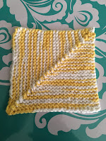 A garter stitch mitered square knit with yellow and white variegated cotton