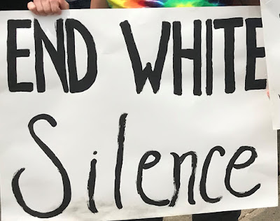White posterboard with 'end white silence' painted in large black letters. One of the protestor's hands is visible as well as a tie dyed shirt.