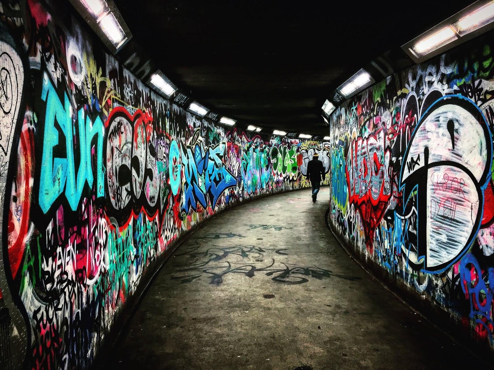 Man walking through subway corridor with graffiti on walls to illustrate blog post about gang warfare
