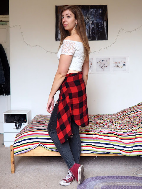 Rematch - outfit of white lace crop top, grey ripped skinny jeans, red & black checked shirt around waist, & red Converse shoes
