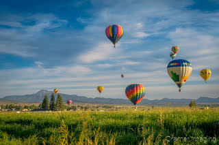 Cramer Imaging's fine art photograph of a hot air balloon cluster floating over a field in Panguitch Utah with a blue partly cloudy sky