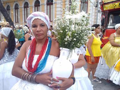 Fotografia colorida de uma mulher negra vestida de branco e com turbante  branca com detalhe em rosa: ela usa colares de contas azuis e vermelhas e muitas pulseiras e anéis; segura um vaso branco com flores do campo também brancas.
