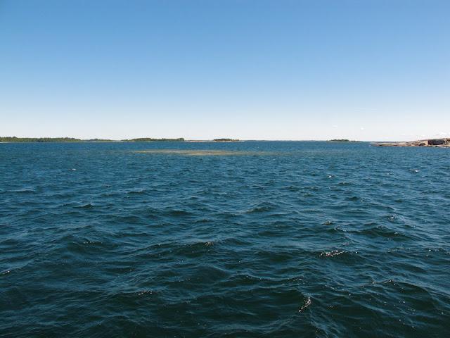 Avomerta, jonka keskellä on vedenalainen riutta. Riutta näyttää sinisen väriseen mereen verrattuna ruskealta alueelta. Kaukaisuudessa siintää myös yksittäisiä luotoja ja saaria.