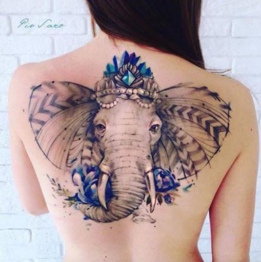 Um elefante veste uma ruiva coroa e está decorado com tons de azul, pérolas, e um padrão de repetição setas junto aos ouvidos.