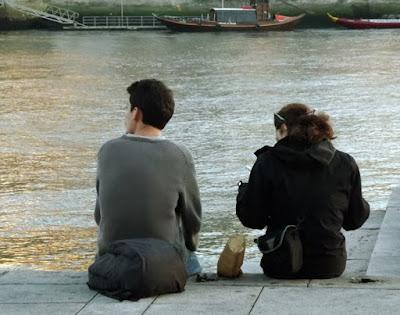 casal sentados na beira do rio comendo castanhas assadas
