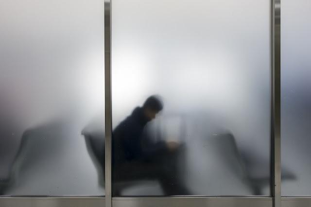 Persona en la sala d'espera d'un aeroport vista a través d'un vidre translúcid