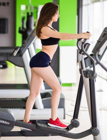 linda mulher fitness de short curto fazendo exercício eliptico na academia cabelo preto