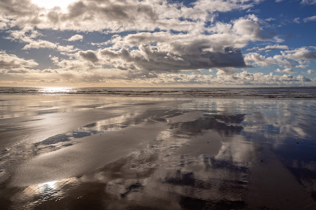 Photo of the clouds reflected in the wet sand at low tide