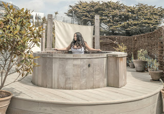 a girl sits inside a wooden hot tub, in a pretty garden area.