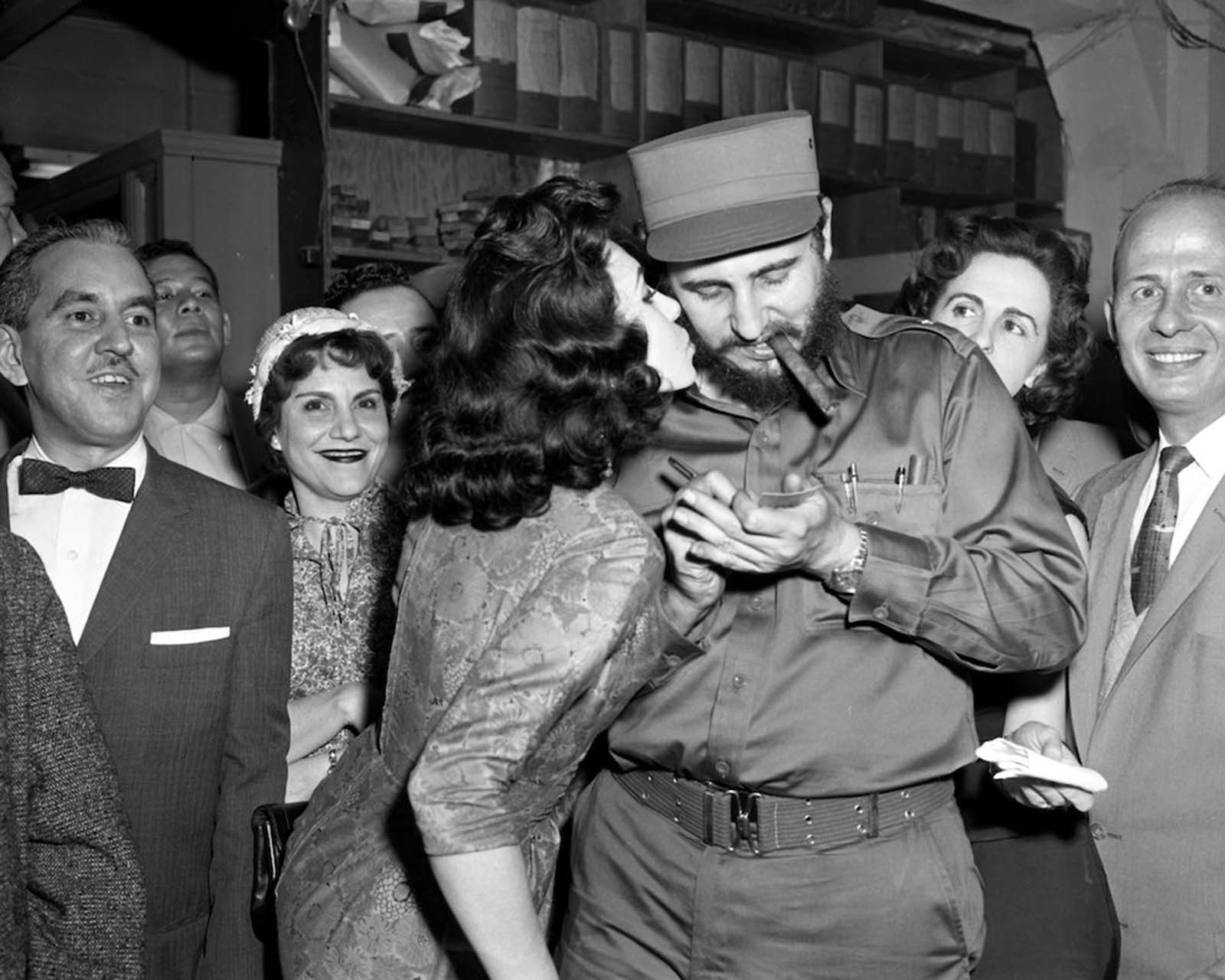 Miss Gladys Feijoo, 19, who was nominated Miss La Prensa of 1959, kisses Castro as he signs an autograph for her collection.