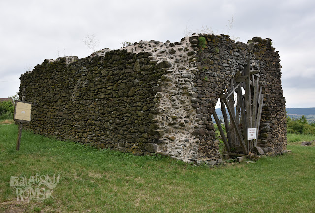 A töttöskáli templomrom sötét színű falmaradványai, jobbra az egykori kapuzat árkádja aládúcolva