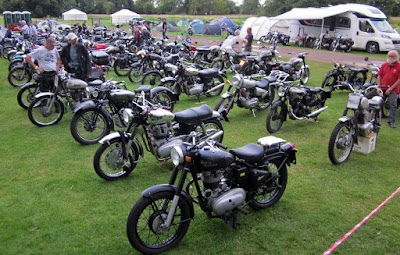 Collection of Royal Enfield motorcycles on the grass.
