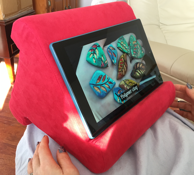 Photo of Flippy pillow stand on woman's lap, holding a Fire HD 10 tablet in landscape orientation