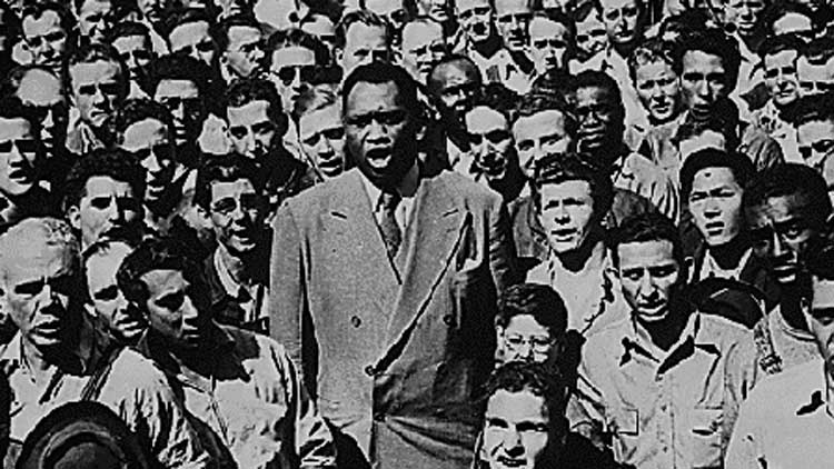 Paul Robeson stands up and sings in Paul Robeson: Tribute to an Artist.