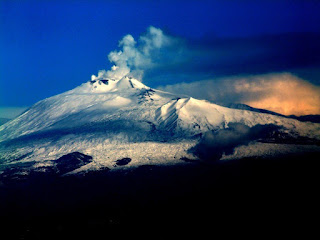 The mighty Mount Etna, smoke emerging from its snow- capped peak, dominates eastern Sicily