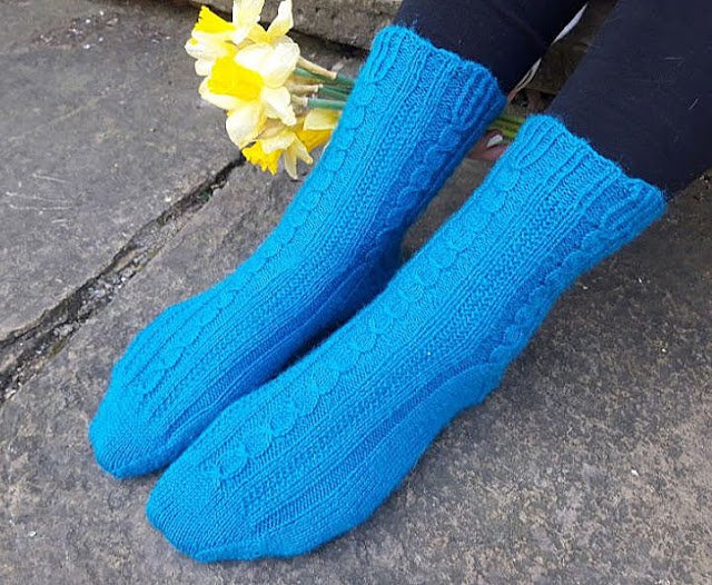 Photo of blue patterned socks being worn.  The feet are resting on a stone flag and there is a bunch of daffodils next to the feet.