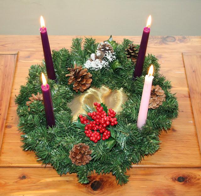 Adventskranz; die Kerzen sind entsprechend den liturgischen Farben für den ersten, zweiten und vierten Advent violett und für den dritten rosa