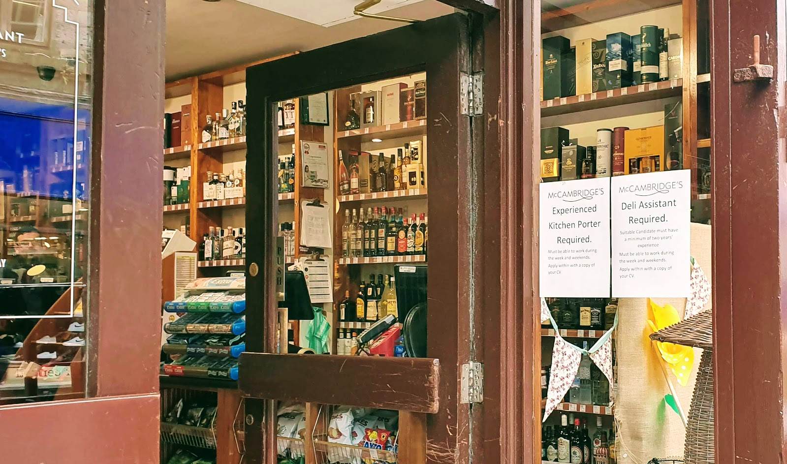 Shop window with help-wanted signs, and till area with an extensive display of whiskys for sale in the Galway store