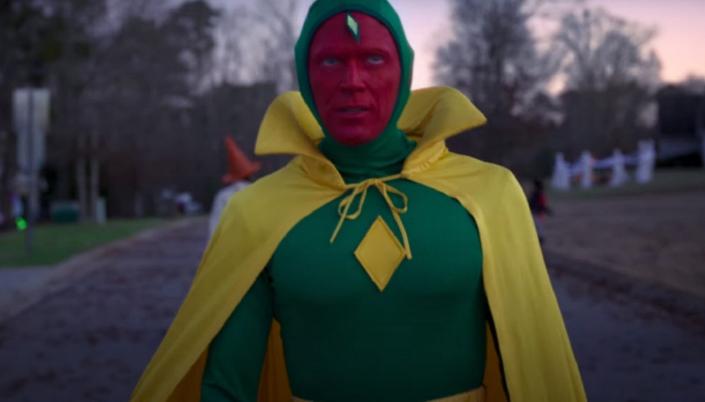 Imagem: o Visão, na fantasia verde e amarela dele, o rosto pintado de vermelho, uma capa amarela longa com uma gola de vampiro e um losango amarelo no peito, andando no meio da rua, em que crianças passam fantasiadas pro Halloween.