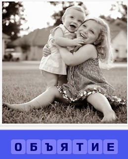 девочка на руках обнимает младенца сидя на траве