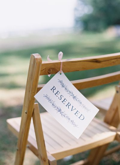 Silla decorada con etiqueta con estampado vegetal y cinta de raso para marcar el sitio de vuestros invitados de boda más allegados.