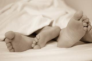 Das Foto zeigt die Füße eines Erwachsenen und eines Kindes unter einer Bettdecke.