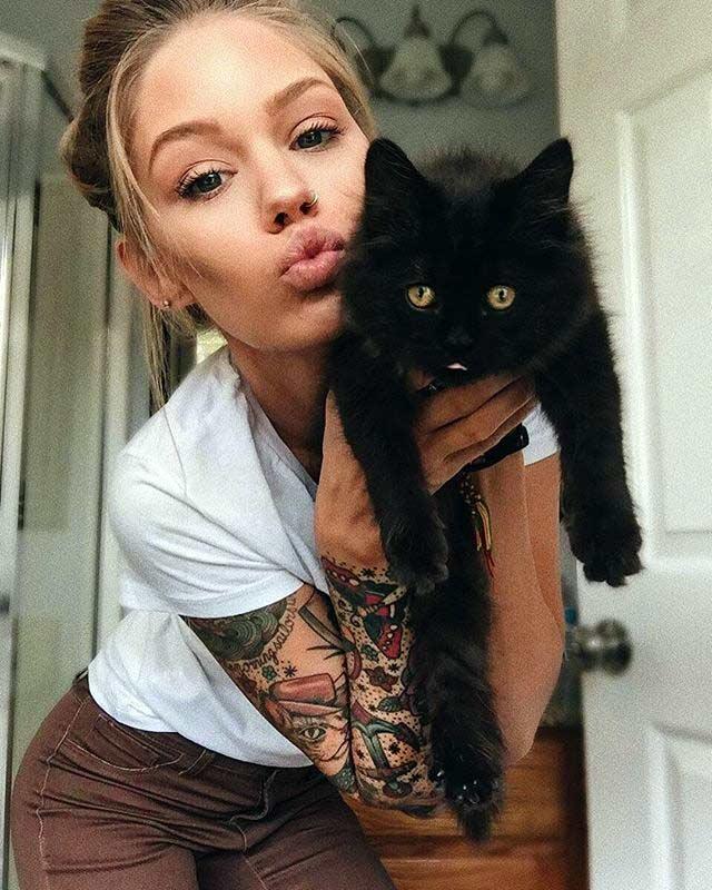 Imagen de chica joven sosteniendo un gato negro.  Ella luce tatuaje de protección