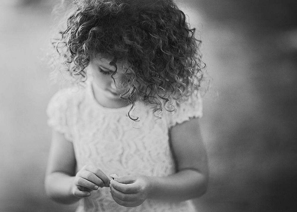 black and white image of a curly little girl with a daisy in her hand