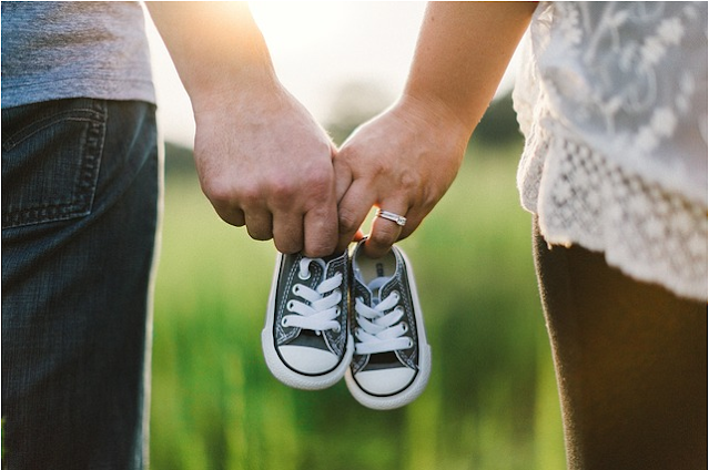 A couple holding baby shoes in their hands