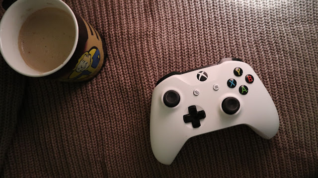Xbox controller with coffee mug on a knitted jumper