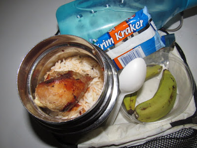 Nigerian school lunchbox meal of rice with chicken and bananas