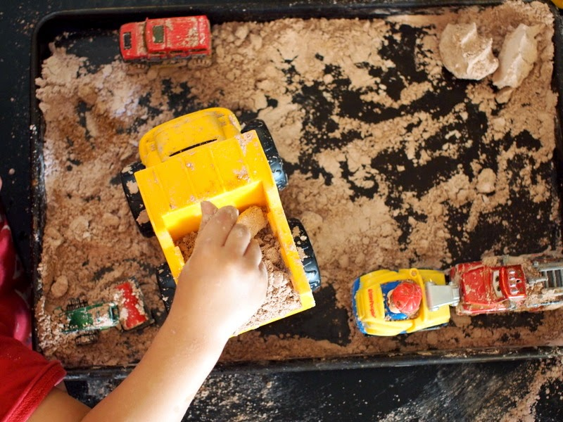 Placing pretend dirt in a dump truck