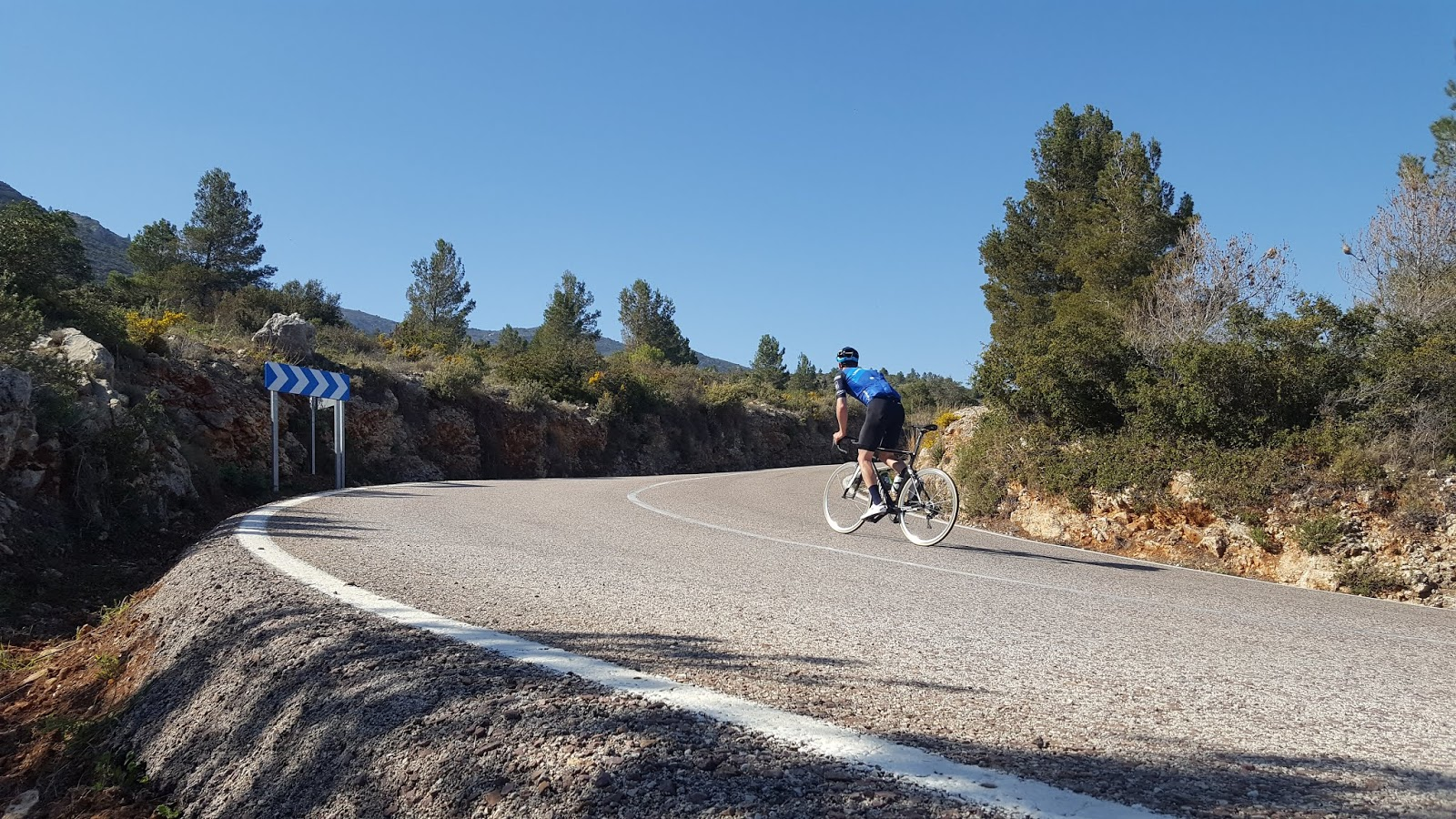 Cyclist riding first right-hand hairpin on northern climb of Coll de Rates