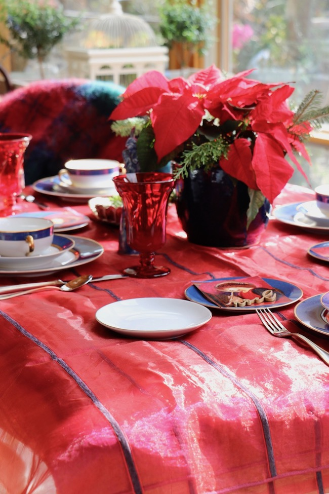Luxurious fabric sets the stage for a blue and red unmistakably Christmas table setting