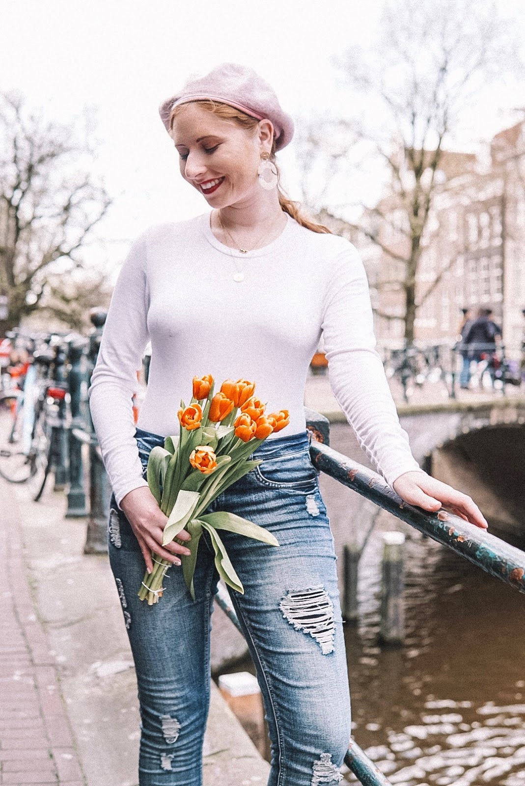 tampa blogger amanda burrows is wearing a cotton on white long sleeve top and distressed denim jeans. she is holding orange tulips in amsterdam.