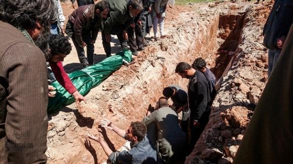 دفن ضحايا الهجمات الكيميائية في قبر في خان شيخون، إدلب، سوريا. AFP