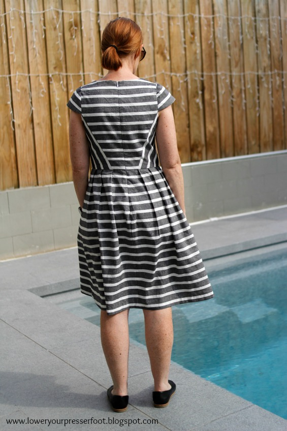 lady modelling a stripe dress in front of a swimming pool