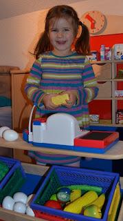 Kind lachend in einem Kaufmannsladen