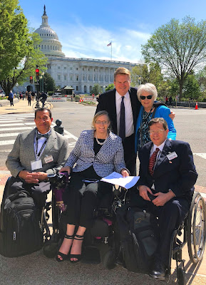 Three wheelchair users and two able-bodied people are dressed in suits, smiling for the camera. The United States' Capital building is in the background
