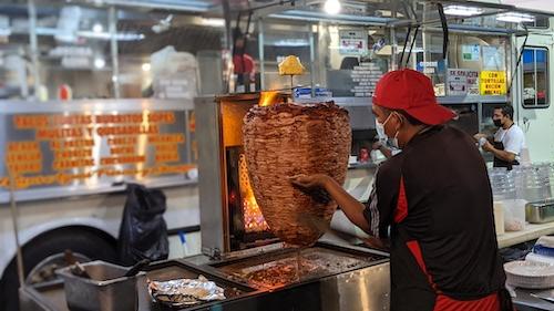 A taquero cuts al pastor meat from the trompo