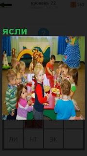 В комнате яслей находятся маленькие дети и играют с воспитательницей