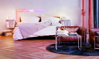 Bed with Bar lighting above on the wall, pink and yellow coloured at right angle shape