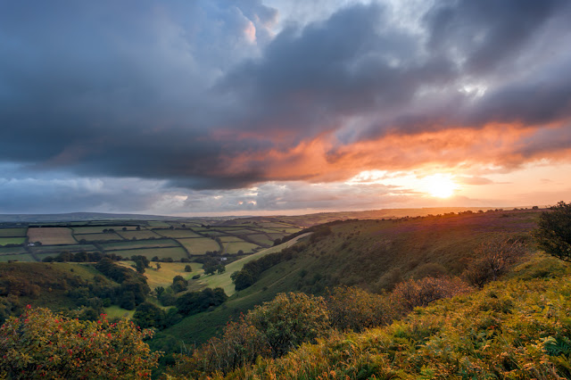 Sun breaks through the clouds at down to light up the Punchbowl in Exmoor