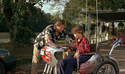 Gary Busey helps Corey Haim with his electric wheelchair in a movie still for the 1985 horror film Silver Bullet, 31 days of Halloween movie review