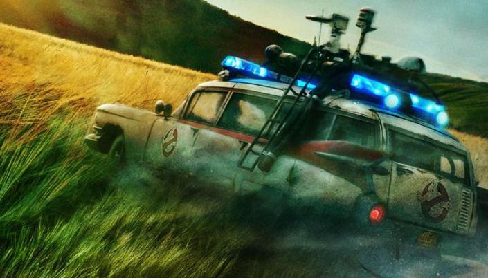 Imagem: um campo de trigo enorme com um carro velho com o símbolo dos Caça-Fantasmas estampado na porta dele.