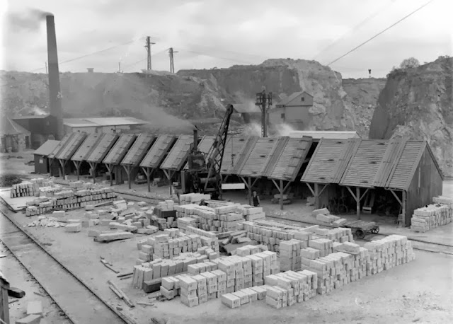 Kemnay Quarries. Aberdeenshire. General view of the mason's yard. Stockpiled finished stone in a variety of sizes all neatly labelled can be seen in front of the masons' sheds. A steam train is seen mounted on a light railway. In the distance is part of No. 2 Quarry with several blondins stretched across the quarry. The roofs of the sheds could open to allow the travelling steam crane to deposit stone inside for the masons to work on.