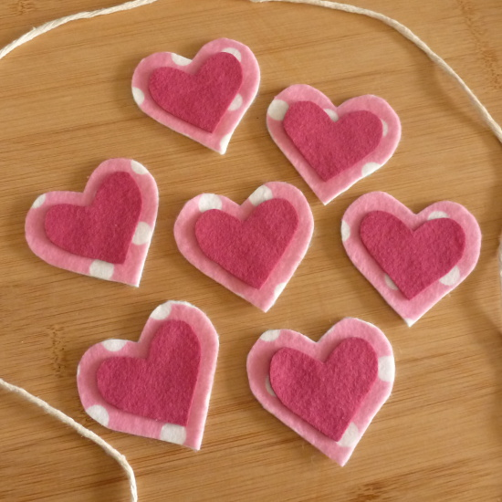 Layering up pink felt hearts to make a banner bunting