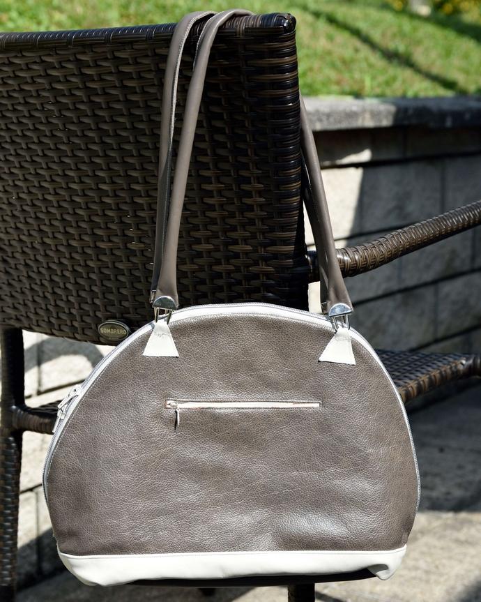Auf der Rückseite der Bogentasche ist ein Reißverschlussfach ins Schlamm-farbene Leder eingearbeitet