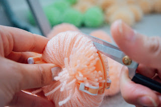Scissors cutting through wool on a pom-pom maker