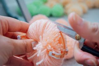 Scissors cutting through wool on a pom-pom maker